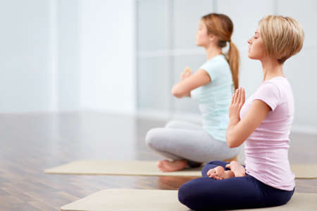 closed club: Young attractive girls in the lotus position Stock Photo