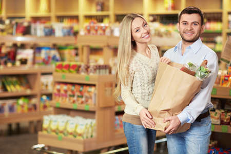 Young couple with package of products in store photo