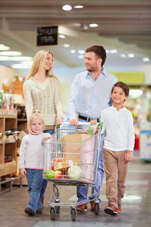 Family with children products with a cart in the store photo