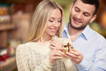 gives: Young man gives a woman gift