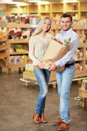 Young couple with a package products Stock Photo - 18661054