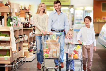 woman shopping cart: Family with children in shop