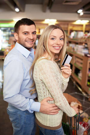 Young couple with a credit card in a store photo