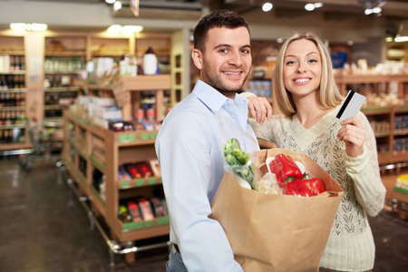 woman credit card: Young couple with a credit card in a store Stock Photo