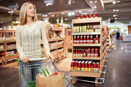food shelf: Young woman with a cart in a store