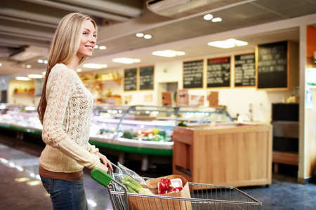 grocery shopper: Young woman with a cart in a store