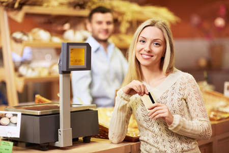 checkout counter: Beautiful girl with a credit card in a store Stock Photo