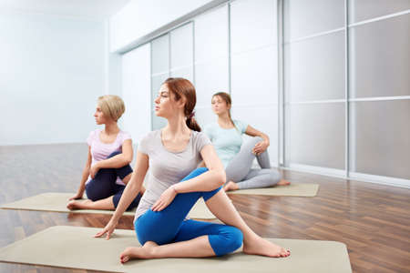 health club: Young attractive girls do yoga Stock Photo