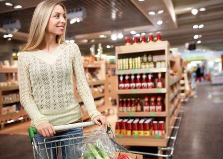 tiendas de comida: Chica joven con un carrito en la tienda