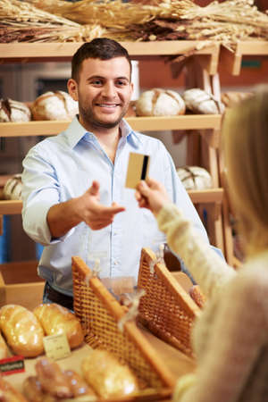bakery store: Attractive girl with a credit card at the counter