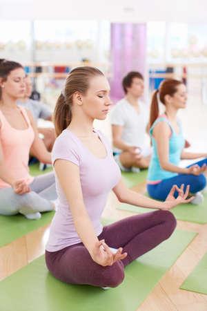 Mladí lidé v lotosové pozici ve fitness klubu Reklamní fotografie