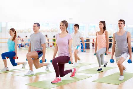 Mladí lidé s jednoručkami ve fitness klubu