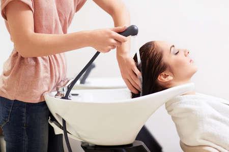 Barber myje dívčinu hlavu do holičství Reklamní fotografie