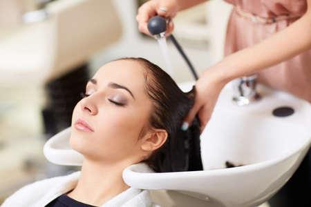 lavare le mani: Barber lava la testa della ragazza nel negozio di barbiere Archivio Fotografico