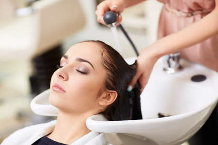 white hair: Barber washes the girls head in the barbershop Stock Photo