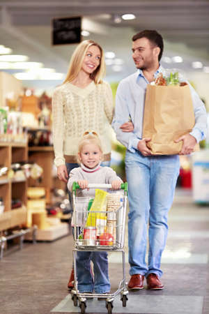 woman shopping cart: Family with child in a store