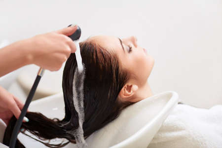 woman washing hair: Washing a head in a barbershop