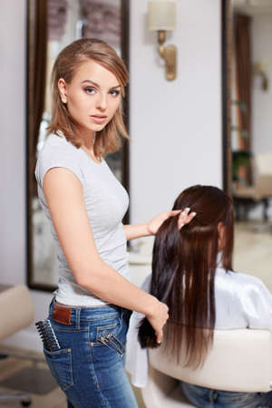 Hairdresser makes hairstyle at the beauty photo