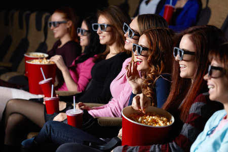 palomitas de maiz: Gente joven sonriente en el cine