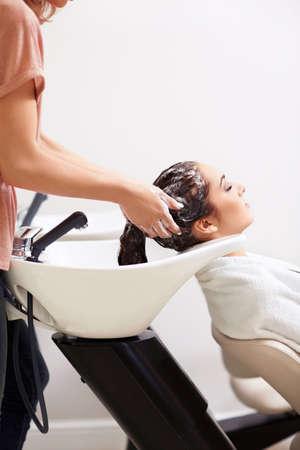 Dívka umýt vlasy v salonu krásy