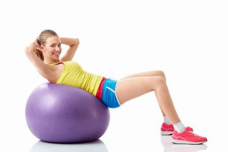 Athletic dívka s fitball na bílém pozadí