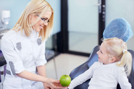 Dentist gives little girl green apple photo