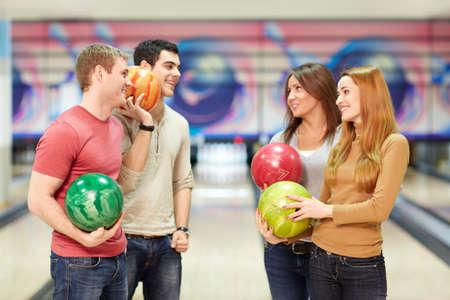 bolos: Sonrientes j�venes en el bowling Foto de archivo