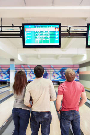 bowling alley: Young people looking at monitor in bowling