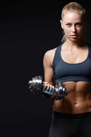 Sports girl with dumbbells on a black background