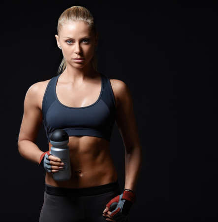 athleticism: Athletic girl with a shaker on a black background