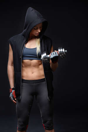 Athletic girl in the hood with dumbbell Stock Photo