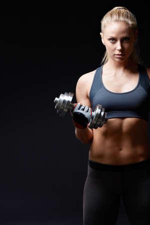 Athletic žena s činkami na tmavém pozadí Reklamní fotografie