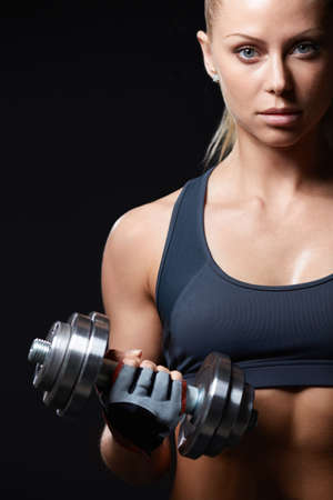Athletic girl with dumbbells on a dark background photo
