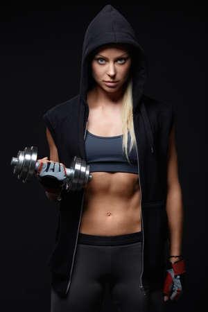 Sportovní dívka v kapuci s jednoručkami