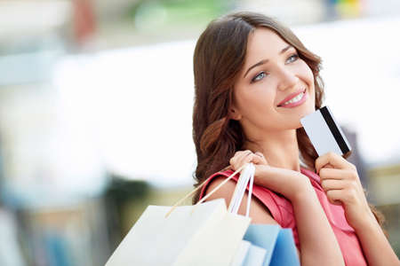 shopping card: Young girl with credit card and shopping bags Stock Photo