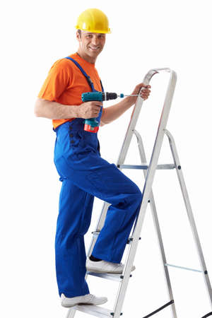 Builder with drill on stepladder Stock Photo
