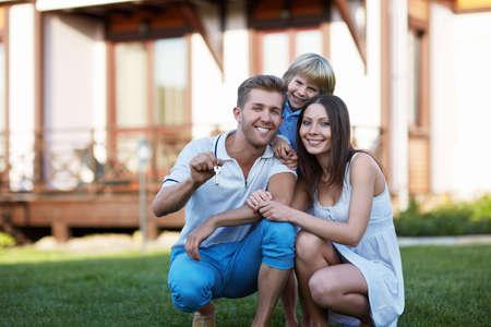 Sourire famille avec enfant autour de la maison Banque d'images