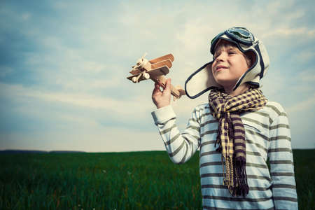 Boy with airplane in a field photo