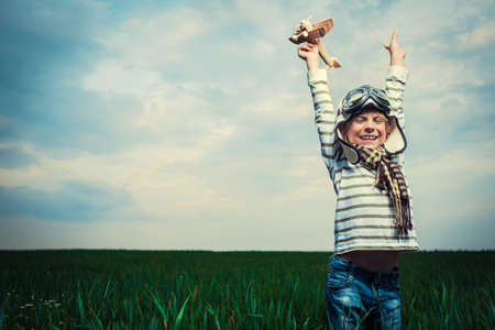 boys playing: Boy with airplane in a field Stock Photo