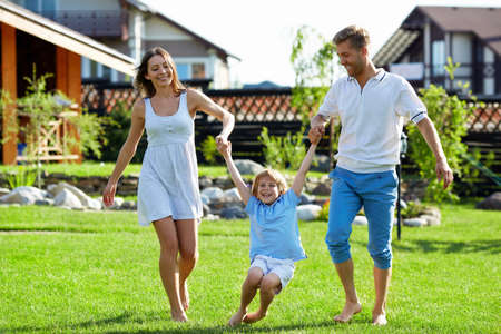 front: Happy family playing on a lawn