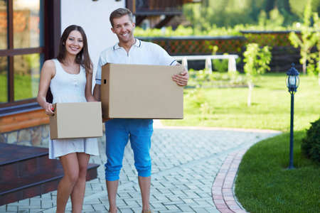 Young couple with boxes by the house photo