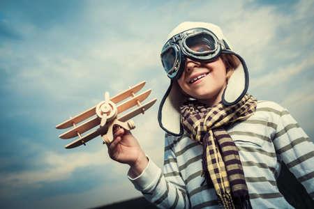 Usmívající se chlapec s dřevěnou letadlem