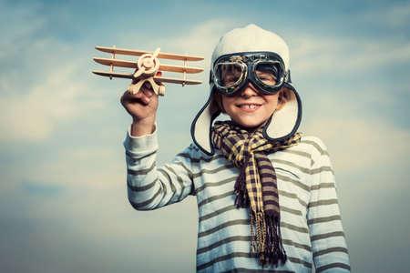 Šťastný chlapec s dřevěným letadlem
