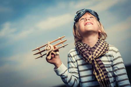 Malý chlapec s dřevěnou letadlem