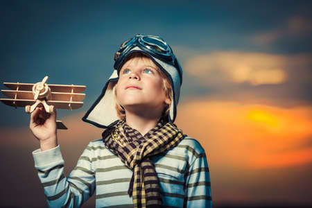 space travel: Boy with plane at sunset