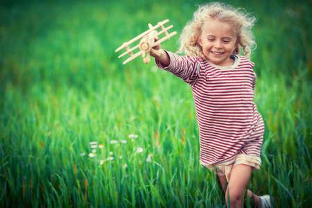 Běh dívka s dřevěný letadlem