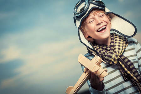 Laughing boy with plane on the background of sky Stock Photo