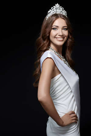 Smiling girl with a crown on a black background