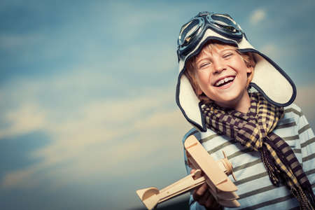 Laughing boy with a plane on the background of sky