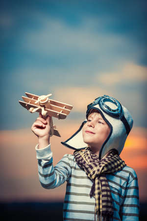 Boy with a plane at sunset Stock Photo